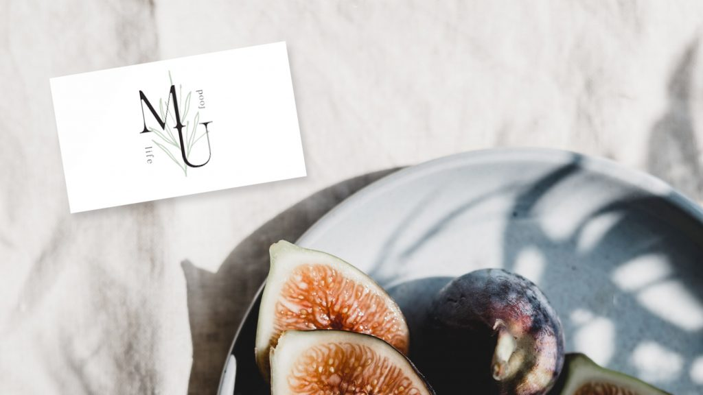 Beautiful business cards near a plate with figs